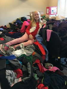 Katie sits on top of a huge pile of coats she collected in 2015.